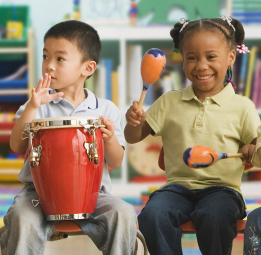 Schoolchildren (4-5) playing musical instruments with teacher in classroom